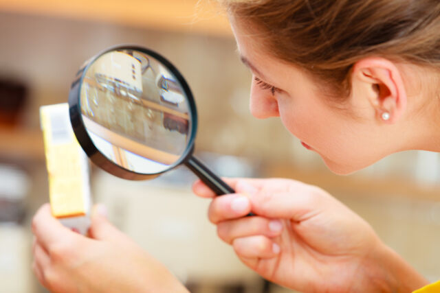 Woman inspecting butter with magnifying glass.